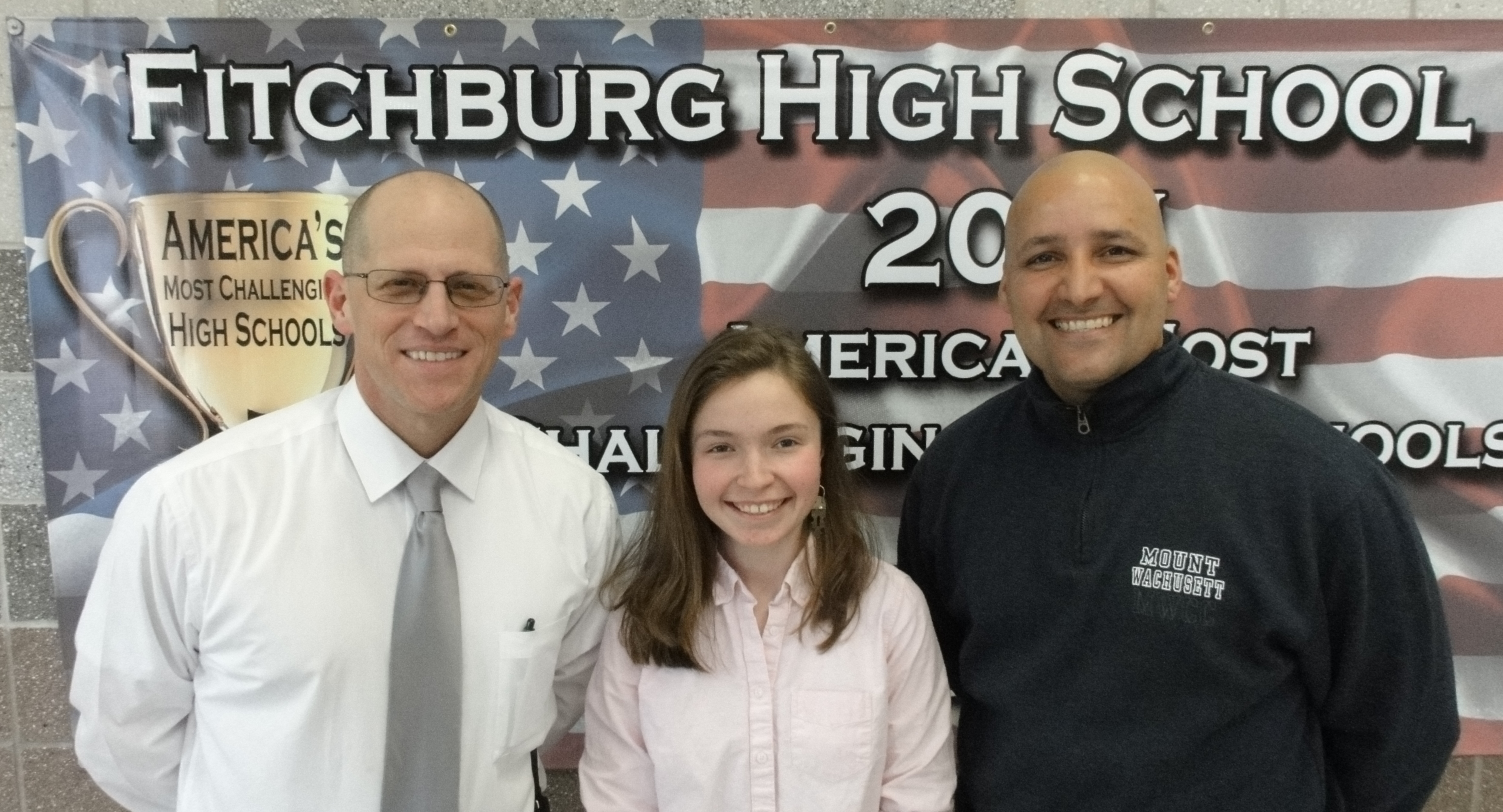 Fitchburg High School Principal Jeremy Roche, left, and Victor Rojas, Assistant Director of the GEAR UP program, right, with scholar Elizabeth Moison