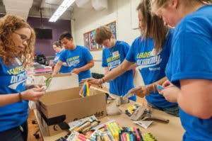 Students working on filling backpacks with supplies