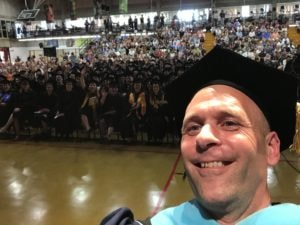 President Vander Hooven taking a selfie from the stage in front of the graduates