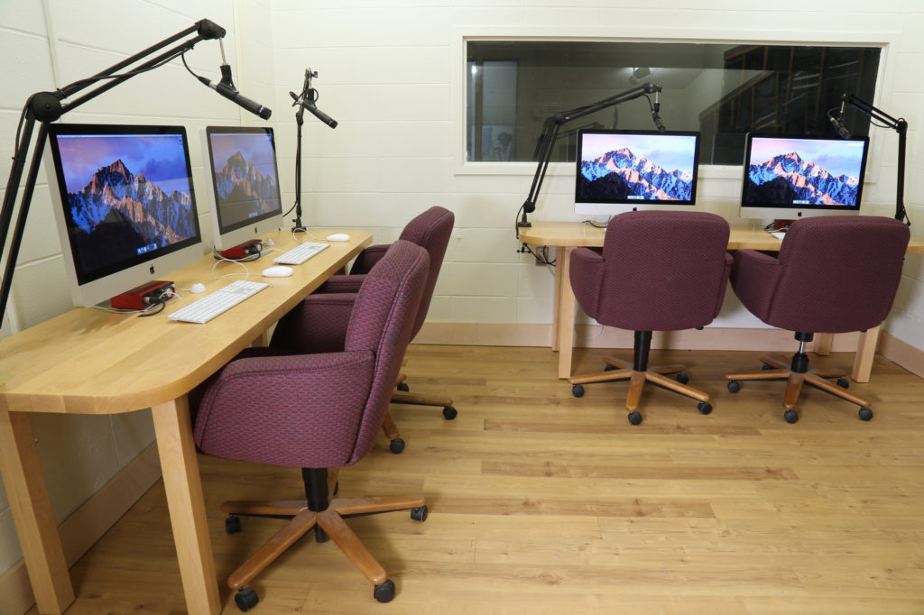 Four Mac computers with microphones and office chairs