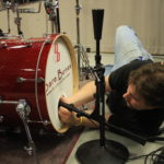 Media Arts & Technology - Audio Student Setting Up a Mic for a Band by the Drums