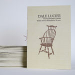 Stack of folded programs and one standing up with Dale Lucier White Sanding Chairs on the front