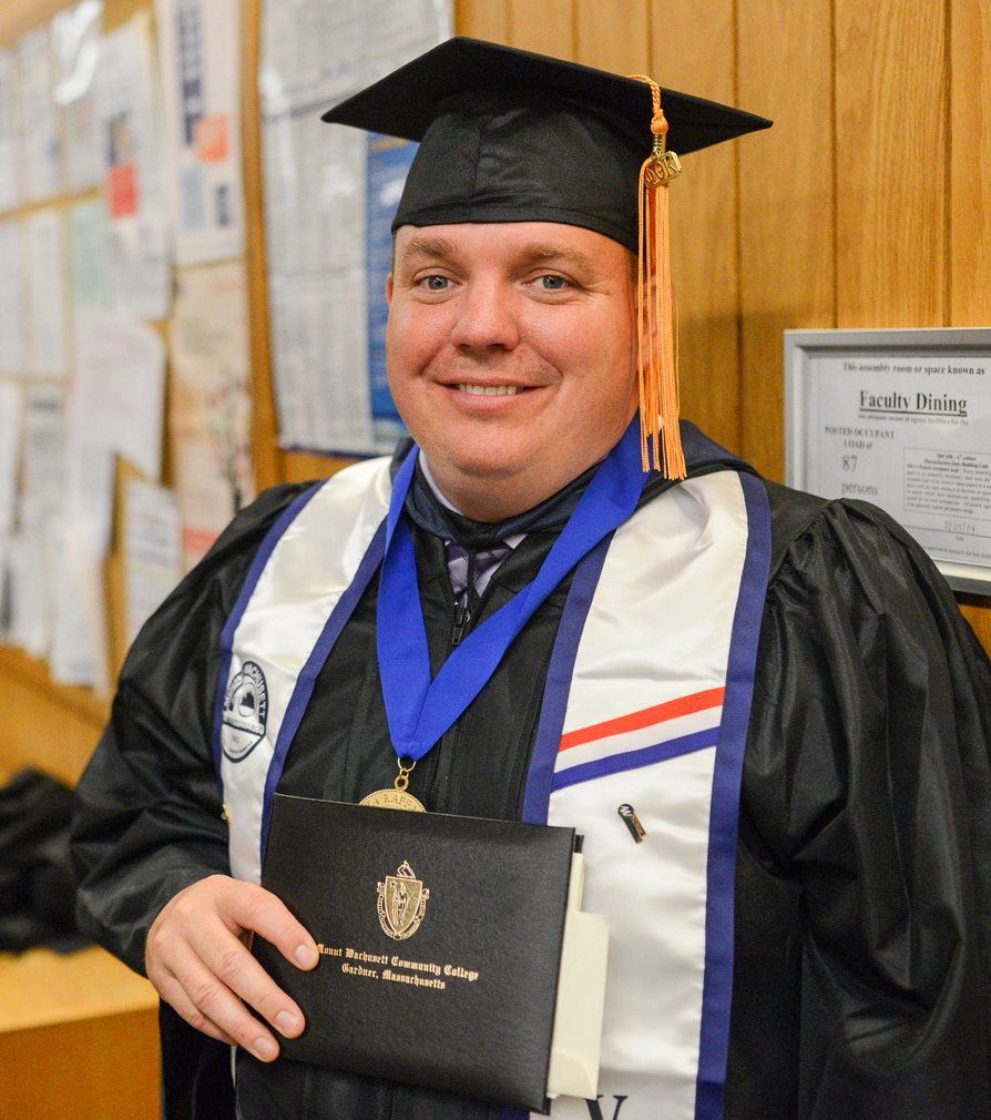 MWCC Veteran Student Tom Berger Standing in His Graduation Regalia with His Diploma