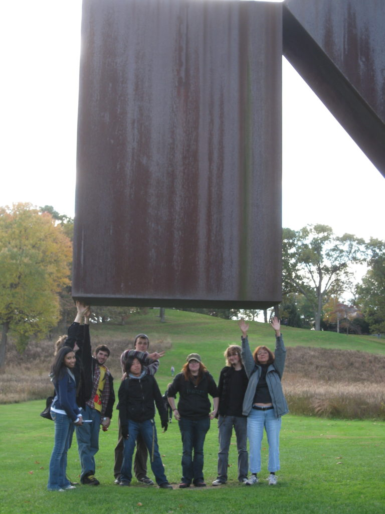 Group of MWCC Art Club students standing under a sculpture in a field