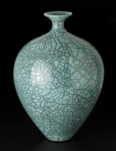 A light teal pottery vase with a crackle effect on a black background, by artist Bob Green
