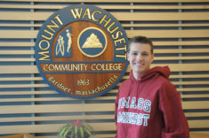 Kyle Deane stands in the main entrance of Mount Wachusett Community College wearing a UMass Amherst sweatshirt. Deane recently graduated early from MWCC and is the first student to successfully transfer to UMass Amherst through the Commonwealth Commitment program.