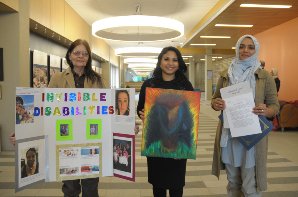 Three women stand in a row holding their projects in front of them.