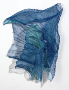 Blue and teal flowing fabric assembled in an abstract presentation on a white/grey background (Art piece is titled Pirouette by Deborra Stewart-Pettengill)