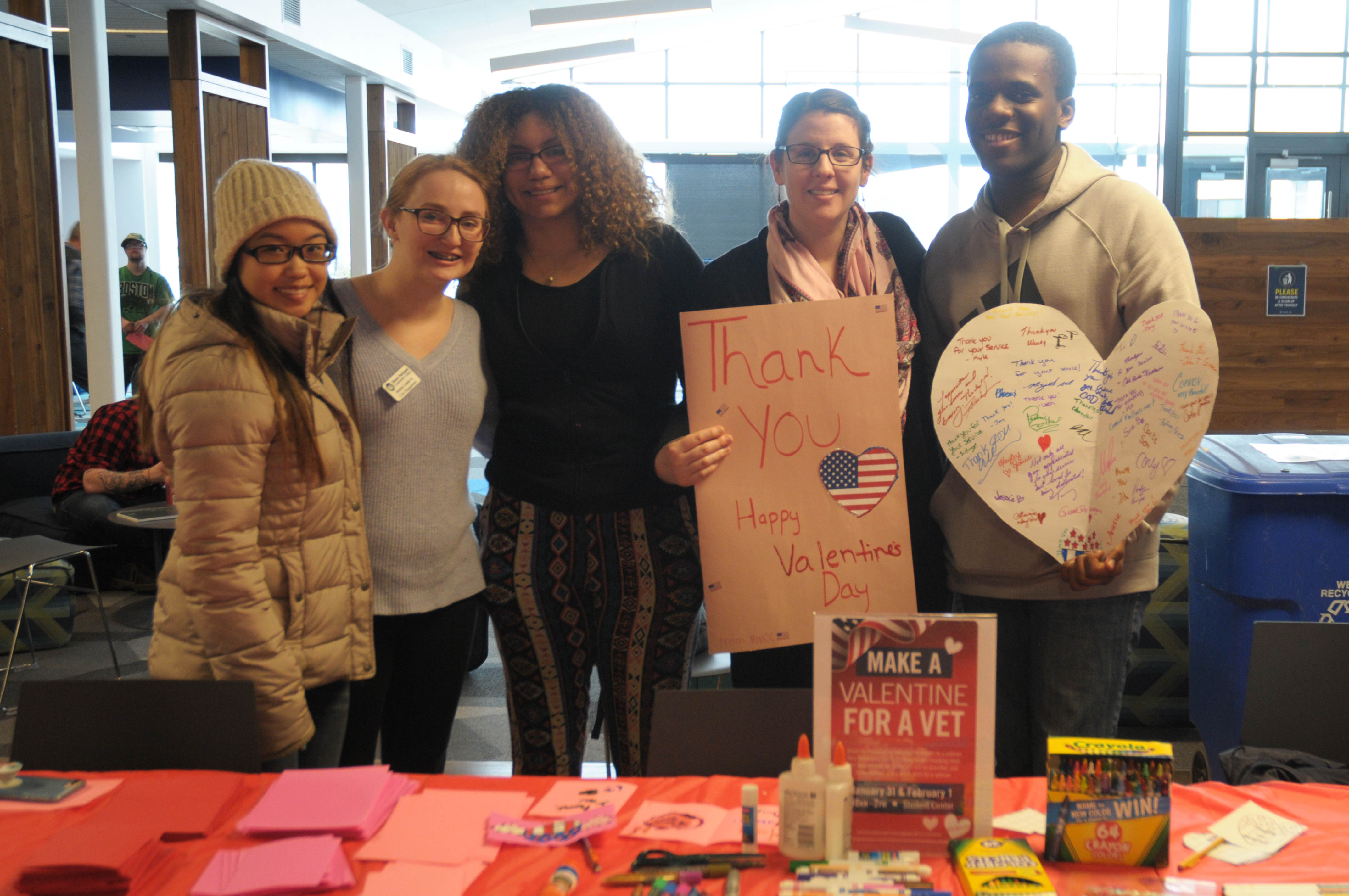 Group of students standing in front of the Valentines for Vets table holding giant cards