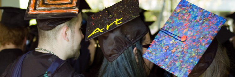 The back of three MWCC Art graduates with decorated mortar boards