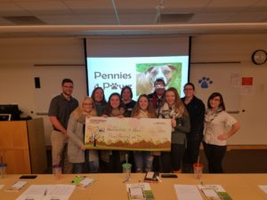 Pennies for Paws Team stands together holding large check