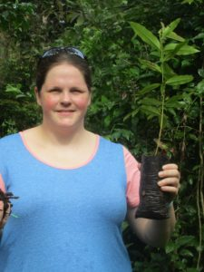 Cristen Comptois is pictured holding a small plant prepared for planting.
