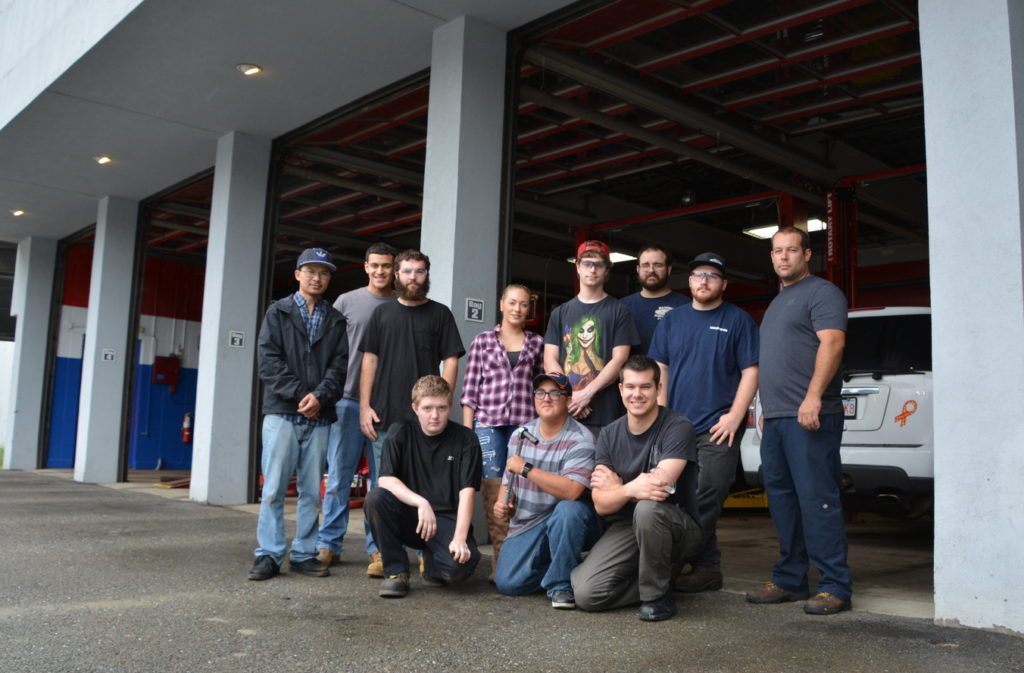 Group of Automotive Students and Professor in front of the six-bay garage