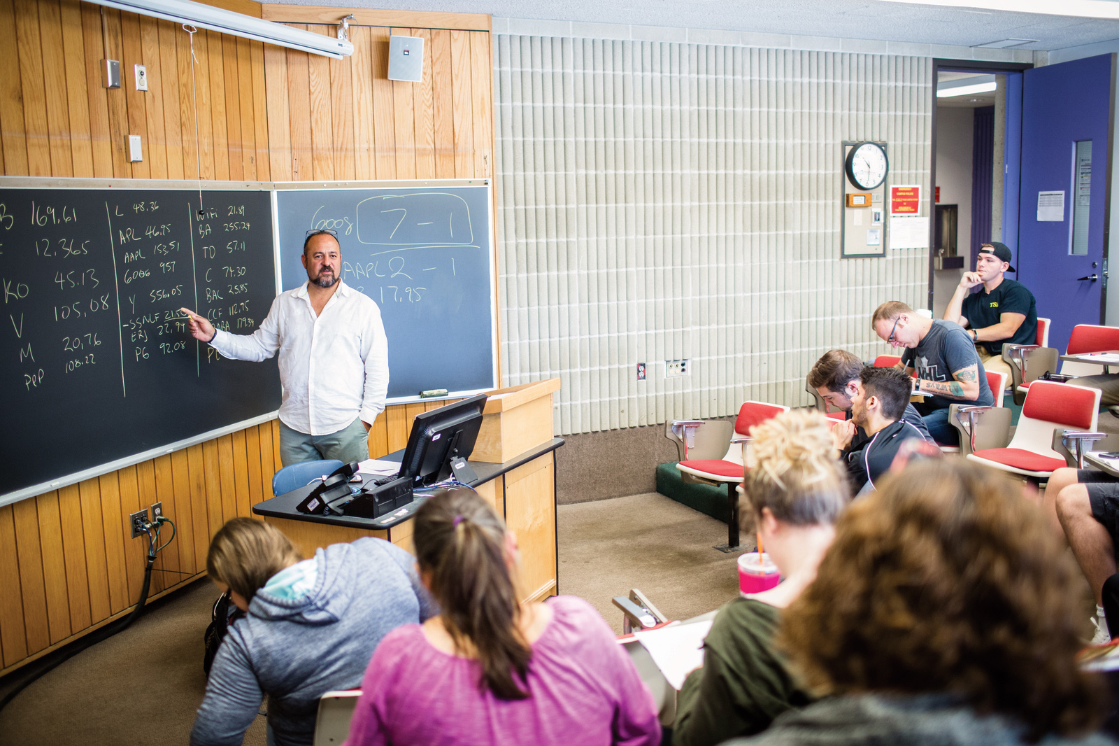 A professor stands in front of a classroom of students as he points at a whiteboard covered with financial figures.