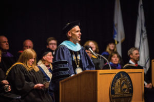 MWCC President Vander Hooven stands in front of a lecturn giving a speech while wearing academic regalia.