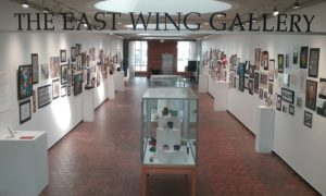 View of the East Wing Gallery hallway and sign with artwork lining the walls
