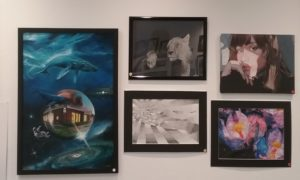 Closeup of 5 art pieces mounted on the white wall (varying subjects)