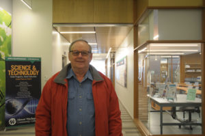 Armand Savoie stands in the hallway of the college's science building.