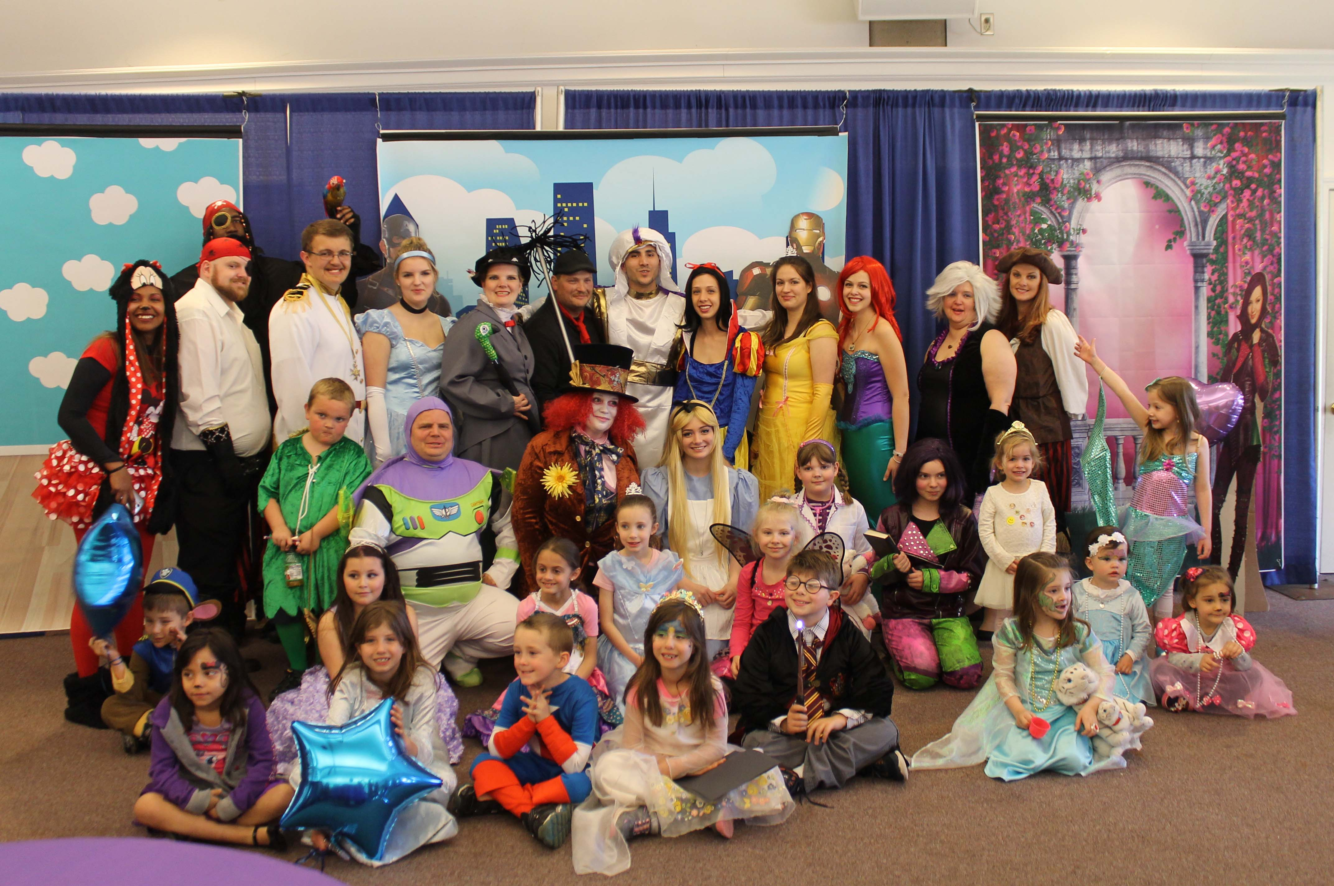 A group of adults and children pose for a group photo in costumes depicting fairy tale and cartoon characters.