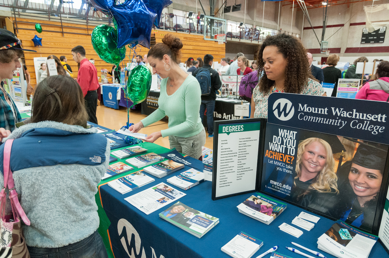 Two MWCC admissions representative stand behind a table while a potential student look at information. There are other college tables set up behind them in a large gymnasium.