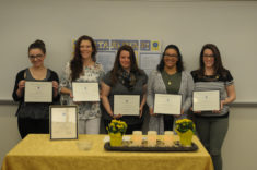 Five female students stand in a row holding certificates.