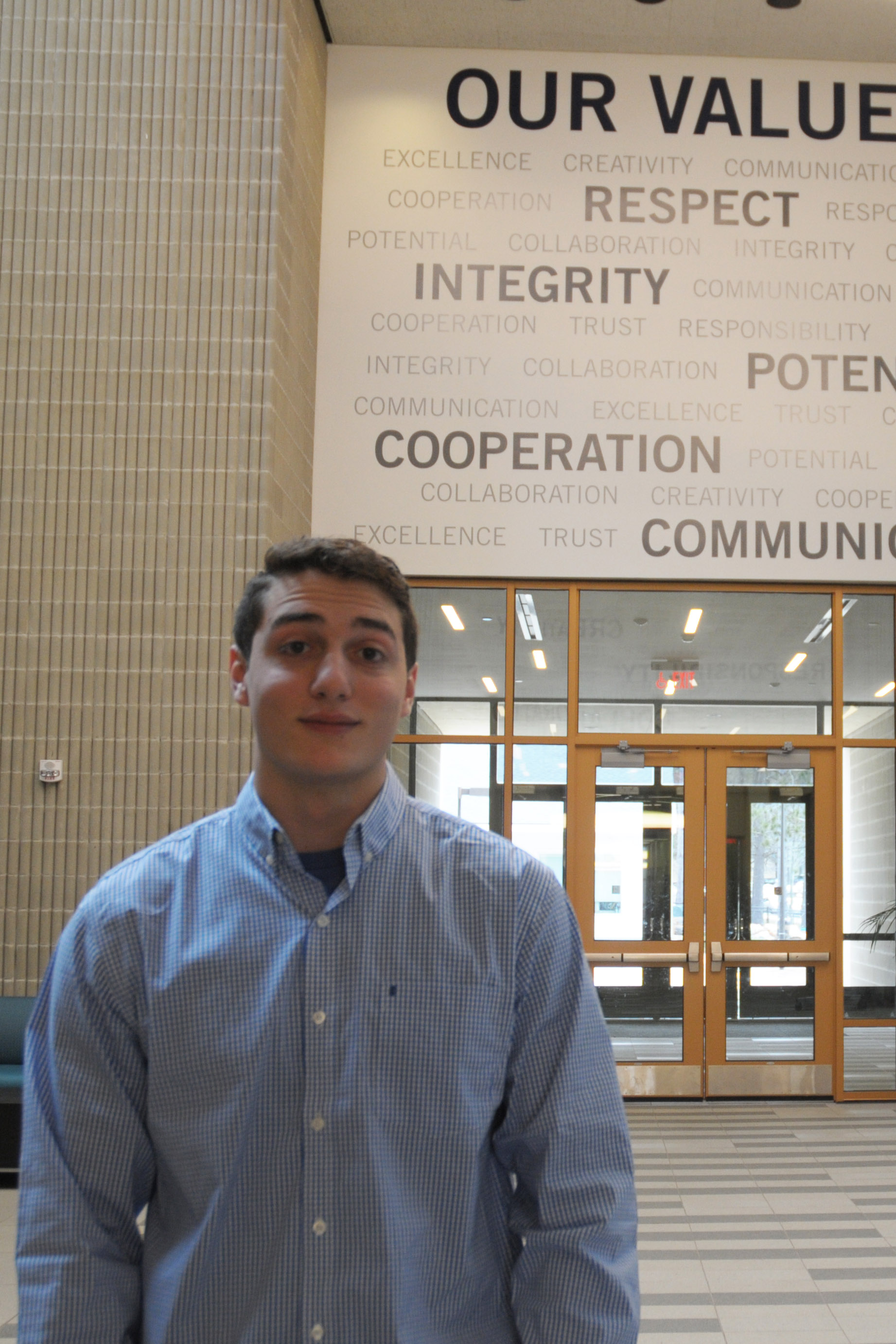 A student stands in a hallway with a poster listing a gathering of positive words behind him.