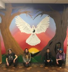 Four student artists crouch in front of a colorful mural they created