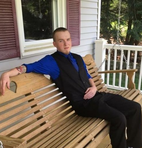 Jonathan Blouin sitting on a bench on a porch
