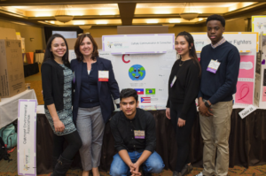 Champion standing next to Culture, Communication, & Connection Venture Team in front of their tri-fold board