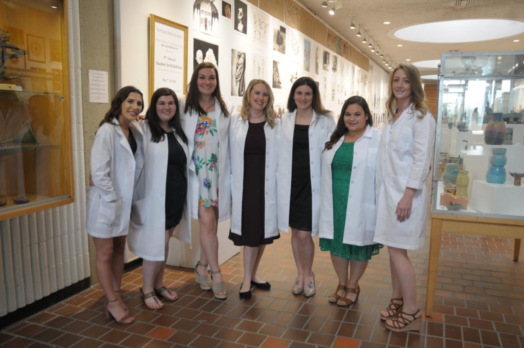 A group of women in dressed up clothing and white lab coats are lined up for a photo.