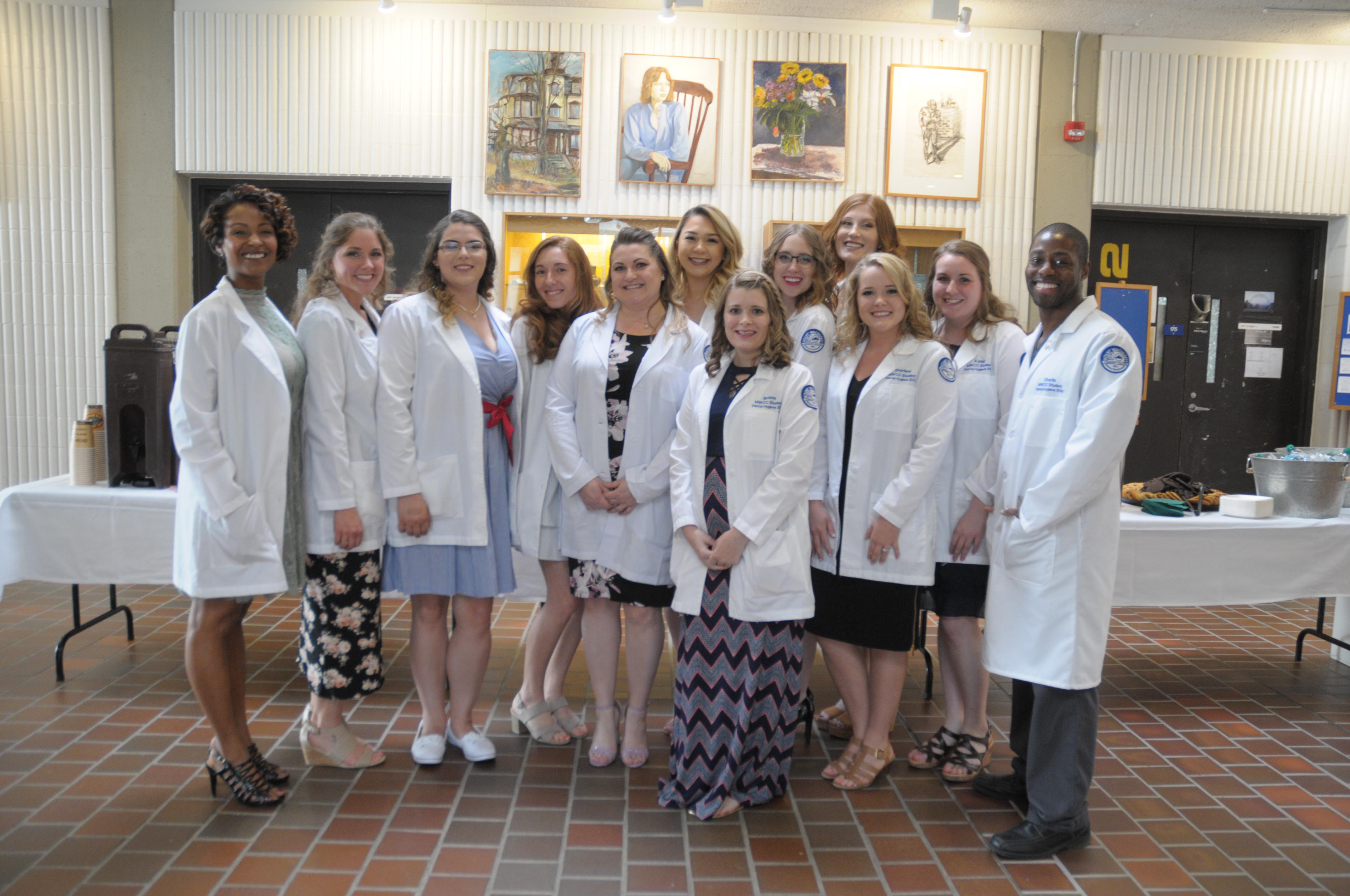 A group of students in white lab coats and nice clothes underneath is lined up for a photo.