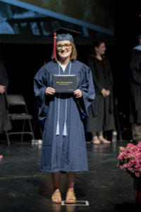 A graduate in a cap and gown holds up their diploma.