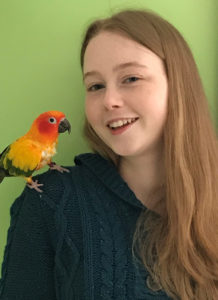 Isabella Marinelli with a colorful bird on her shoulder