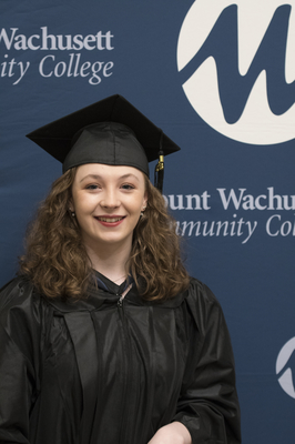 A student is pictured in a graduation cap and gown.