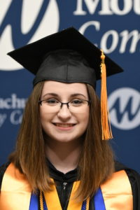 A female student is pictured in her cap and gown from the shoulders up.