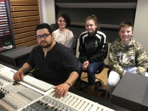 College student sitting in front of the mixing board with three middle school students behind him