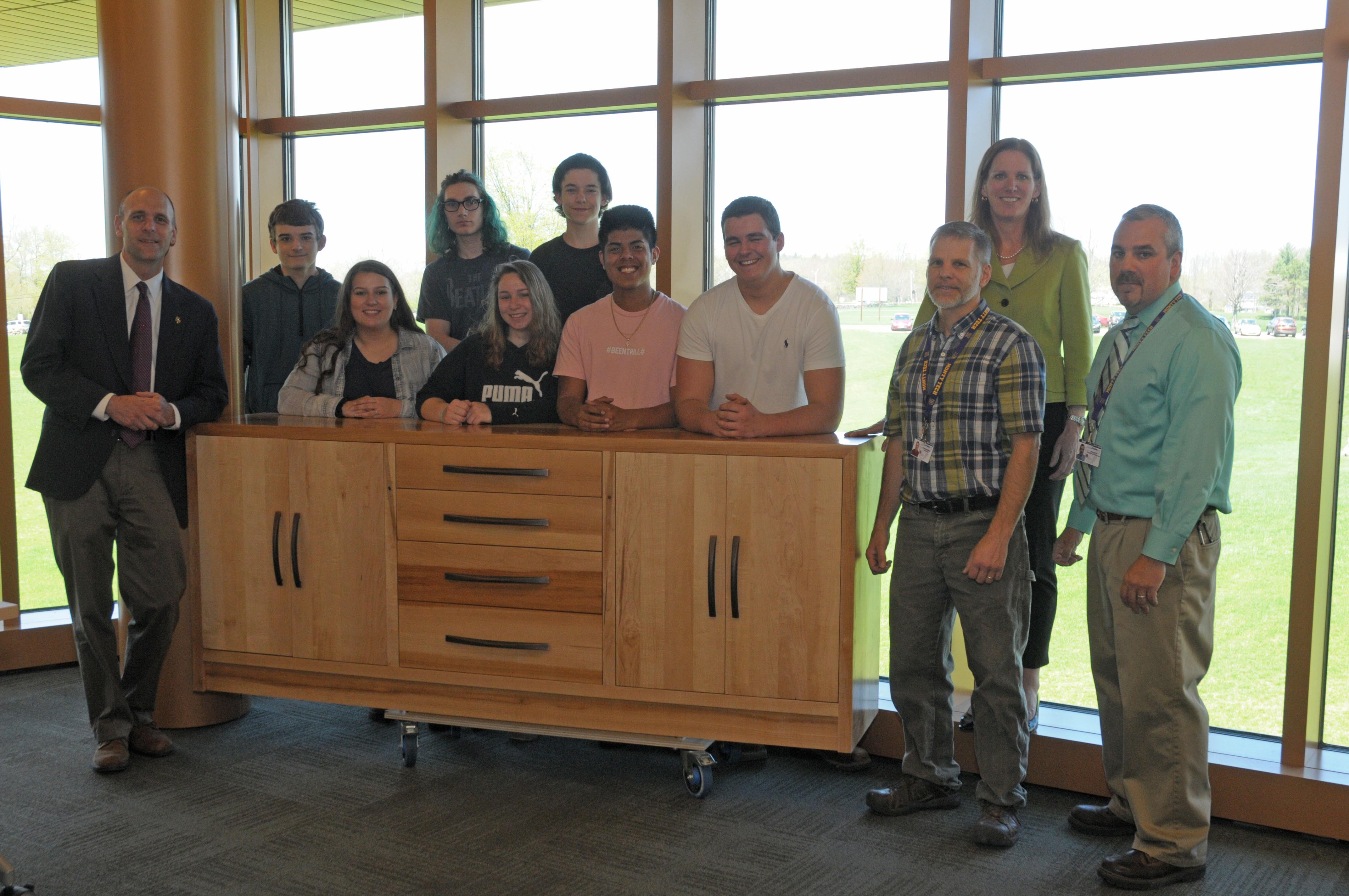 A group of students and school administrators stand in front of a piece of furniture that is roughly 3 feet tall, 12 feet long and with multiple drawers.