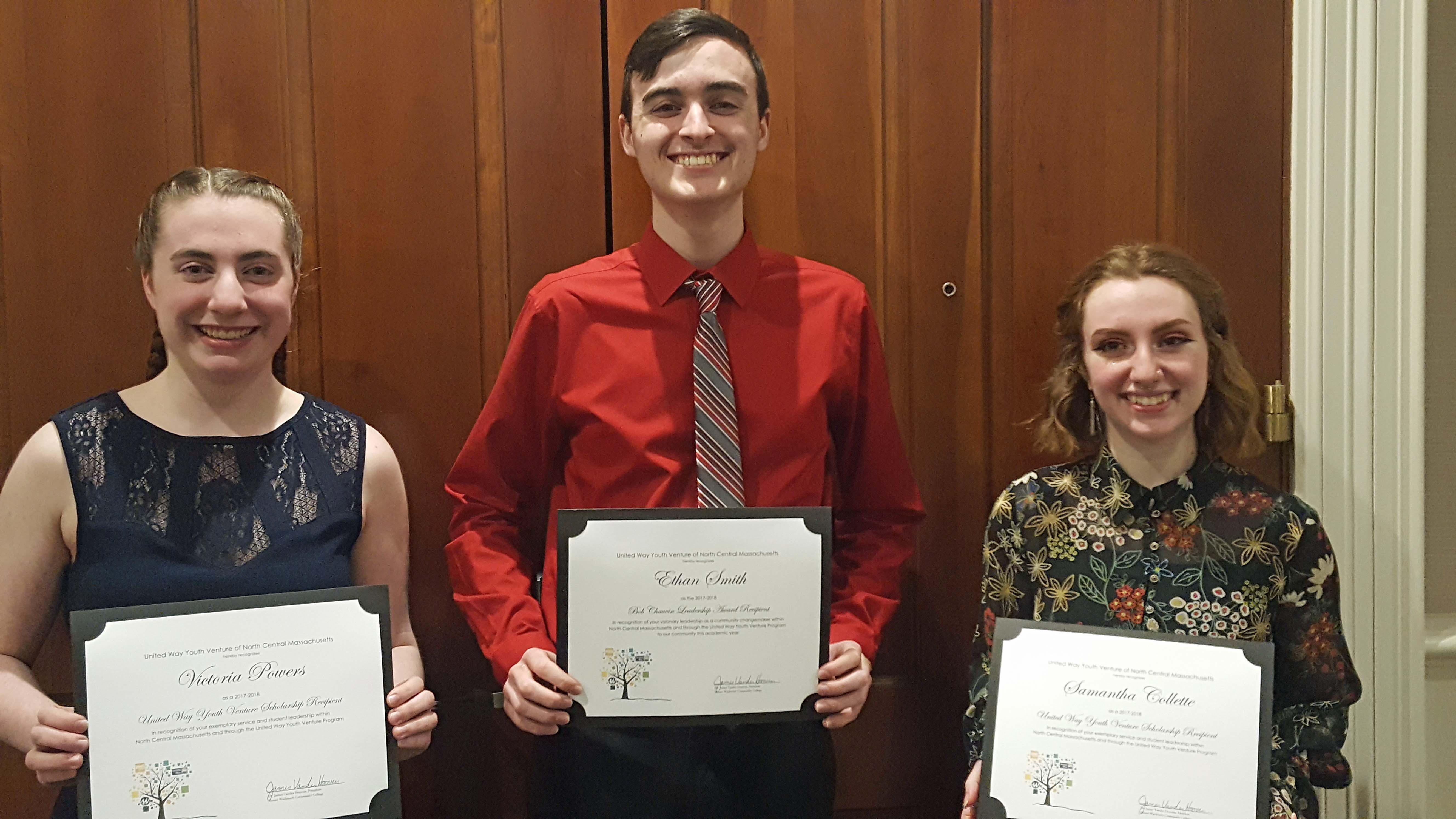 Three students stand in a row holding certificates.