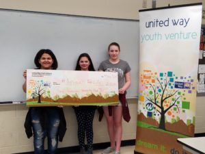 Three girls holding big check