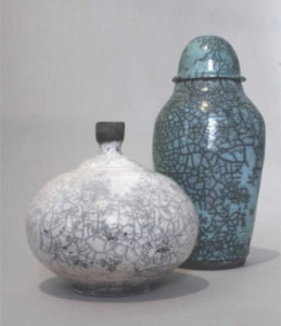 Two raku fired ceramic pieces, one short, wide, white vase, the other a tall thinner teal vase
