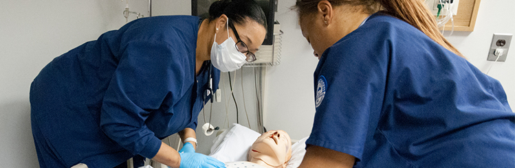 Two female nursing students attend to a simulated patient in bed