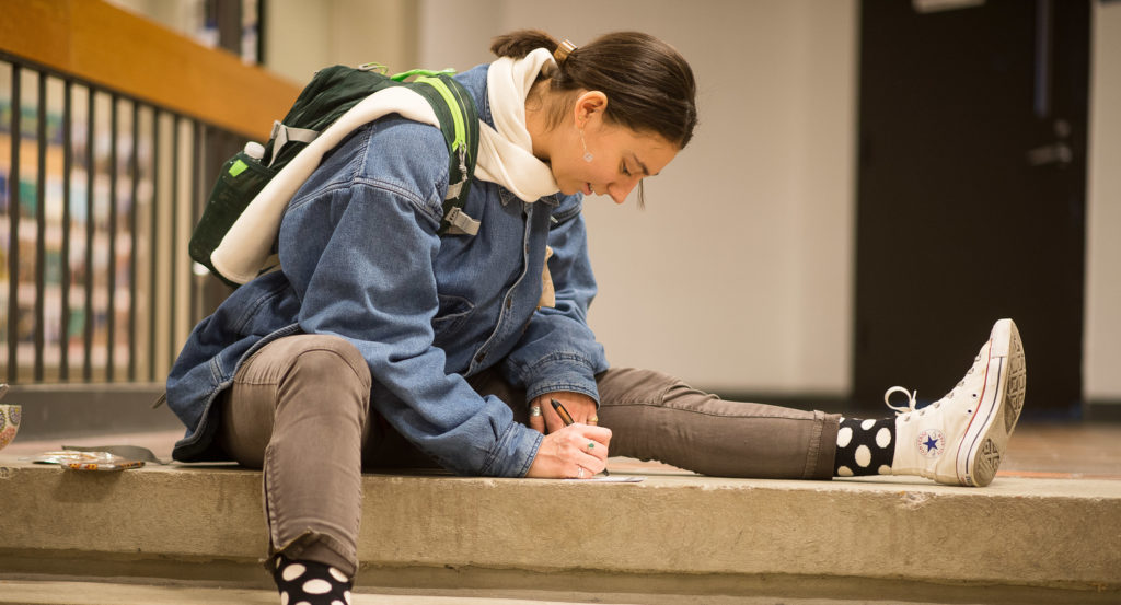 Female student writing while sitting on steps
