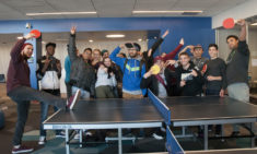 Large group of students in front of the ping pong table.