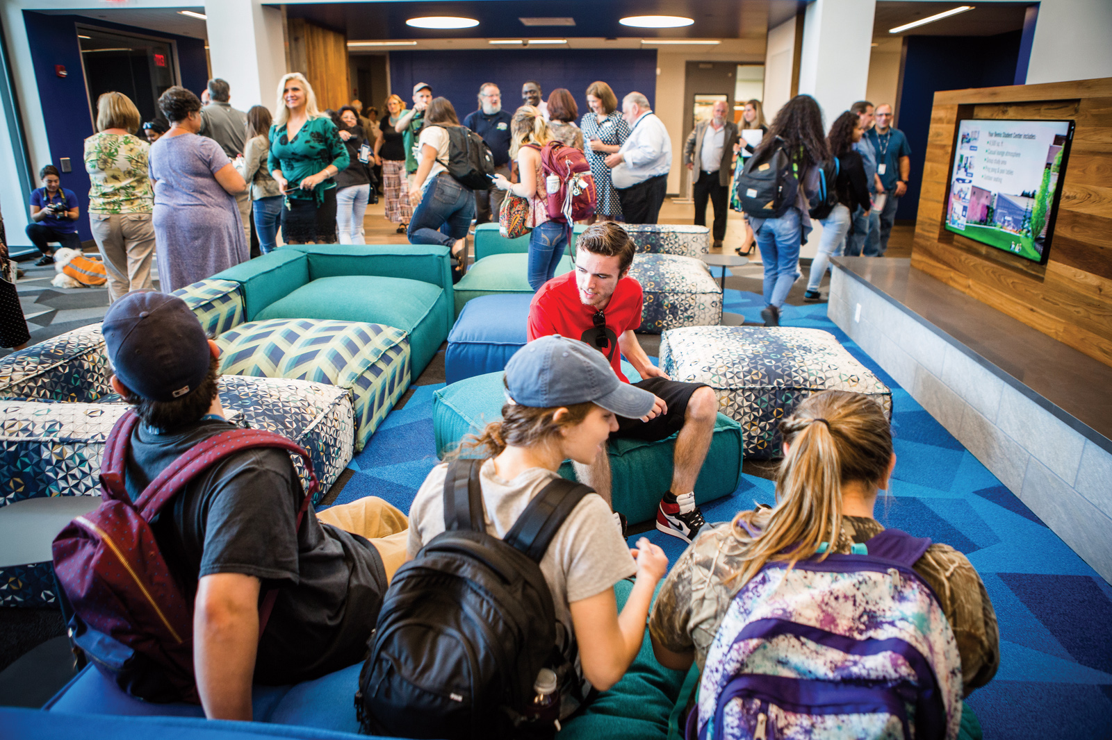 A group of people are gathered in a large social space.