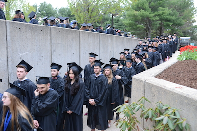A group of students are lined up as they enter the auditorium for commencement ceremonies.