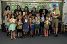 A group of adults stand with first graders.
