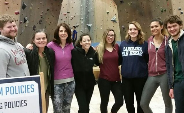 Group of students with their advisor in front of an indoor rockclimbing wall