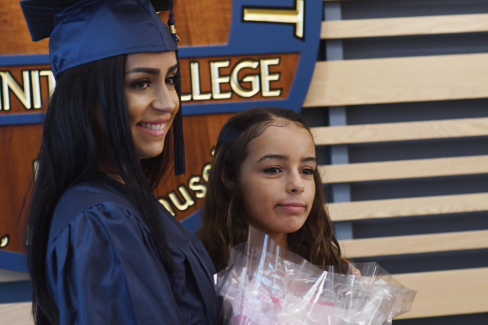 A woman in a graduation outfit poses with her daughter for a photo.