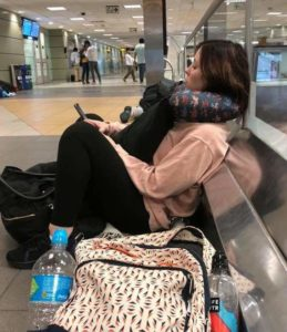Adrienne sitting on the airport floor