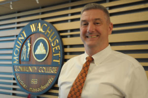 Peter Sennett stands in front of the college's seal.